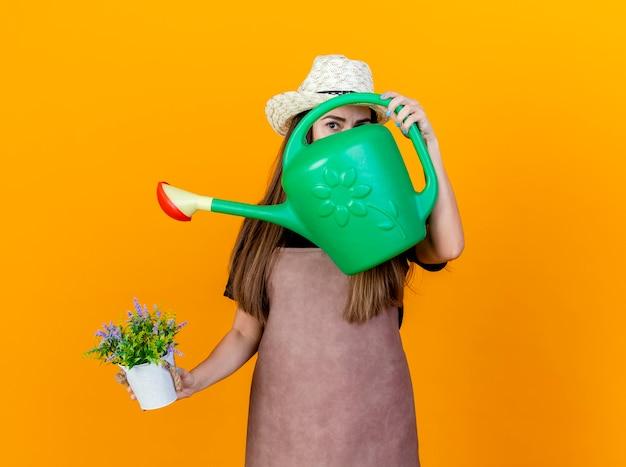 Guardando la fotocamera bella ragazza giardiniere che indossa uniforme e cappello da giardinaggio che tiene fiore in vaso di fiori e viso coperto con annaffiatoio isolato su sfondo arancione
