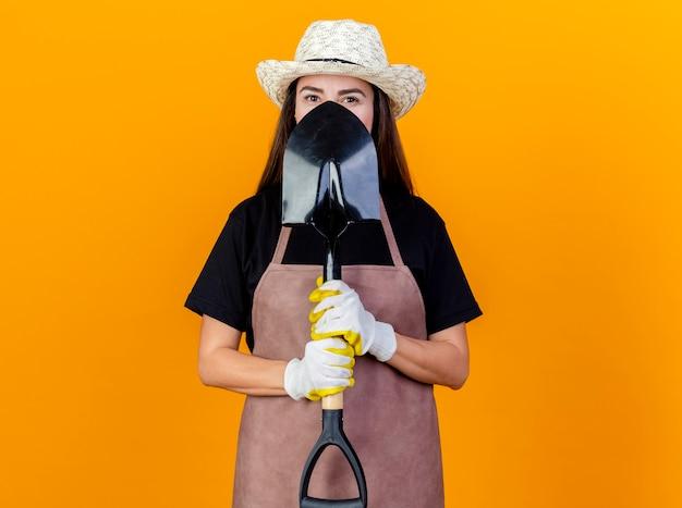 Guardando la fotocamera bella ragazza giardiniere indossa uniforme e cappello da giardinaggio