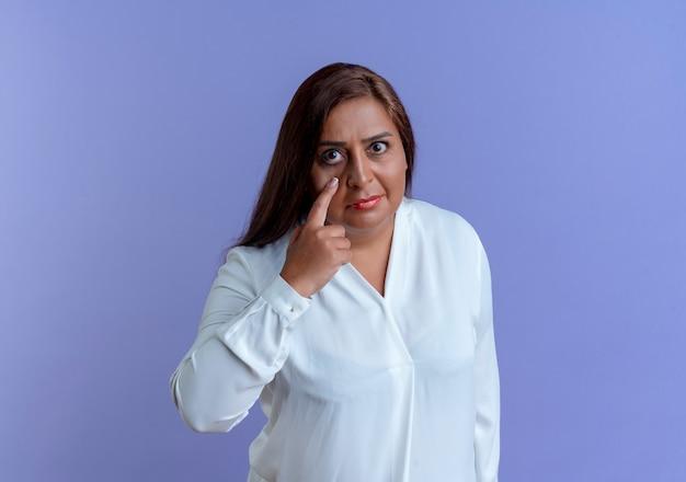 Guardando la fotocamera casual indoeuropea donna di mezza età mettendo il dito intorno agli occhi