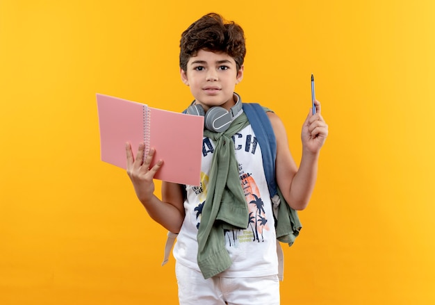 Looking at camera little school boy wearing back bag and headphones holding notebook and pen isolated on yellow background