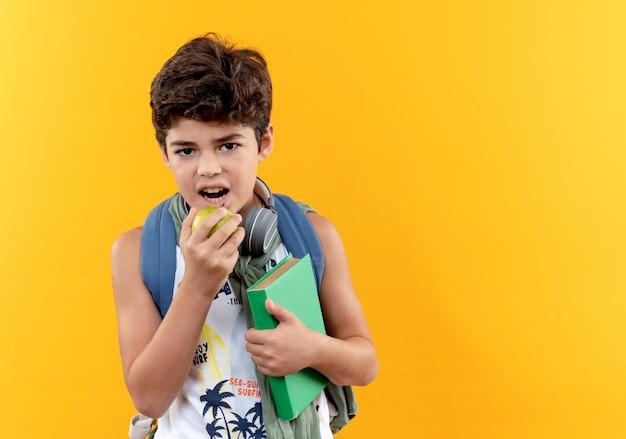 Guardando la fotocamera piccolo scolaro indossando la borsa posteriore e le cuffie che tengono il libro e morde la mela isolato su sfondo giallo
