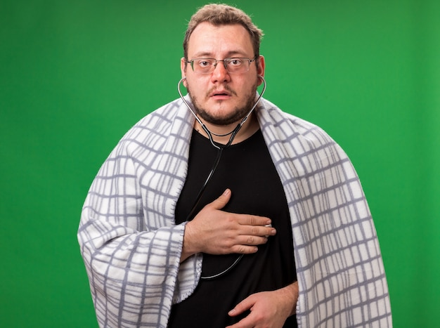 Looking camera middle-aged ill male wrapped in plaid listening to his own heartbeat