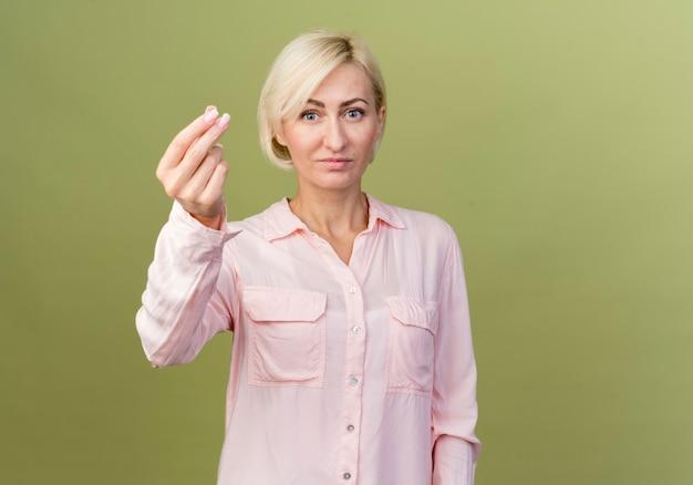 Guardando la fotocamera compiaciuto giovane donna bionda slava che mostra il gesto di punta