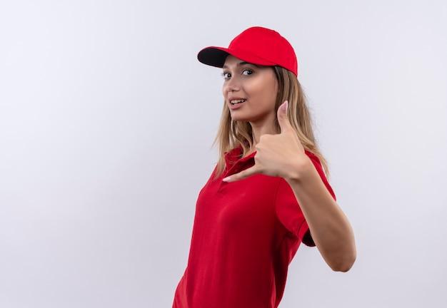 Guardando la fotocamera lieta giovane ragazza di consegna che indossa l'uniforme rossa e il cappuccio che mostra il gesto di chiamata telefonica isolato su priorità bassa bianca