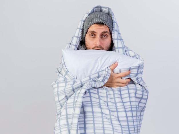 Guardando la telecamera dispiaciuto giovane uomo malato che indossa cappello invernale e sciarpa avvolto in un plaid