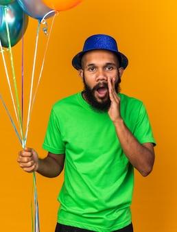 誰かを呼び出す風船を保持しているパーティーハットを身に着けている若いアフリカ系アメリカ人の男がカメラを探しています