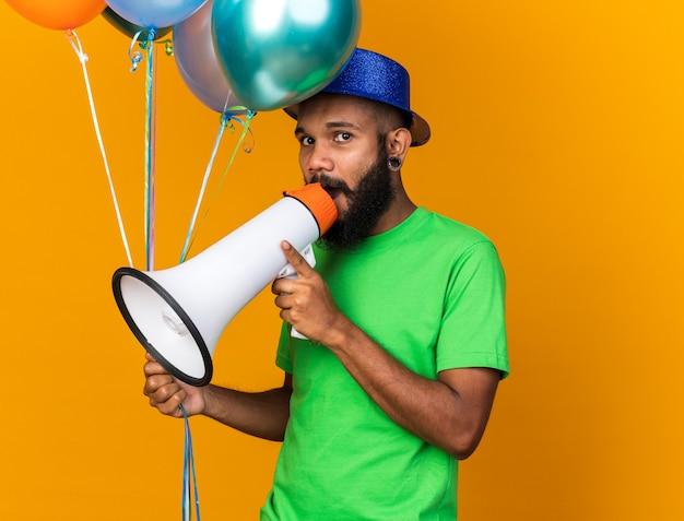 풍선을 들고 파티 모자를 쓰고 카메라를 찾고 젊은 아프리카계 미국인 남자는 확성기에 말한다