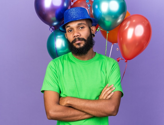 Looking camera young afro-american guy wearing party hat standing in front balloons crossing hands