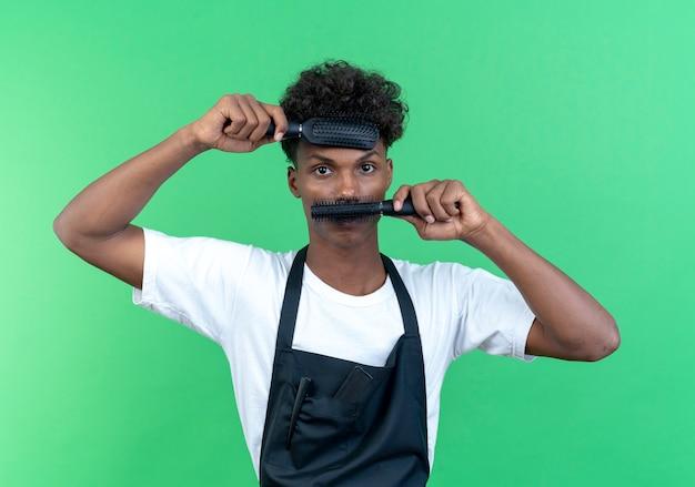 Guardando la telecamera giovane afro-americano barbiere maschio indossa uniforme coperto fronte e bocca con pettini isolati su sfondo verde