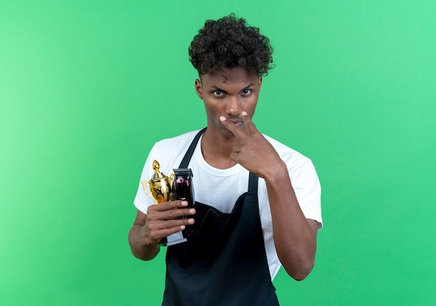 Looking at camera young afro-american male barber wearing uniform holding winner cup and showing watching you gesture isolated on green background