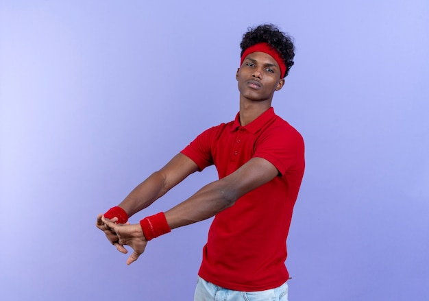 Guardando la fotocamera giovane uomo sportivo afro-americano che indossa la fascia e il braccialetto che allunga il braccio isolato su priorità bassa blu