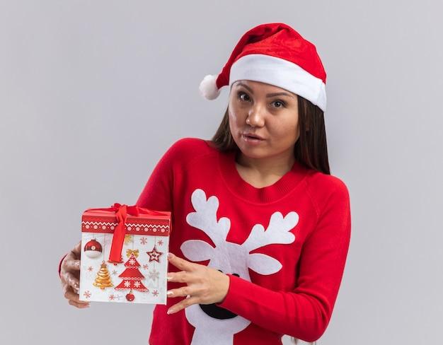 Guardando la telecamera giovane ragazza asiatica che indossa il cappello di natale con un maglione che tiene in mano una confezione regalo isolata su sfondo bianco