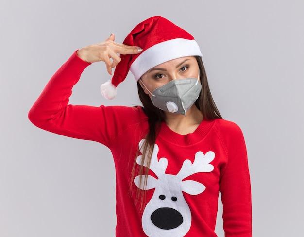 Guardando la fotocamera giovane ragazza asiatica che indossa il cappello di natale con maglione e mascherina medica che mostra il gesto della pistola isolato su sfondo bianco