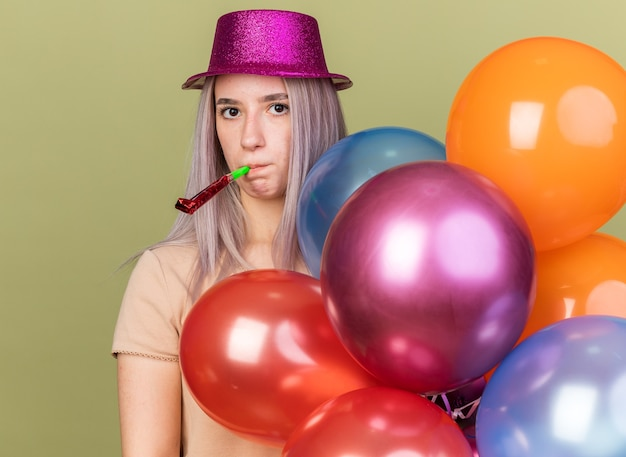 Looking at camera young beautiful girl holding balloons blowing party whistle