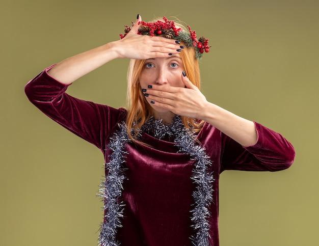 Guardando la fotocamera giovane bella ragazza che indossa un abito rosso con la corona e la ghirlanda sul collo coperto con le mani sulla fronte e la bocca isolata su sfondo verde oliva