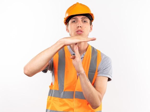Guardando la telecamera giovane costruttore in uniforme che mostra il gesto di timeout