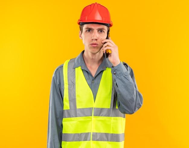 Guardando la telecamera il giovane costruttore in uniforme parla al telefono