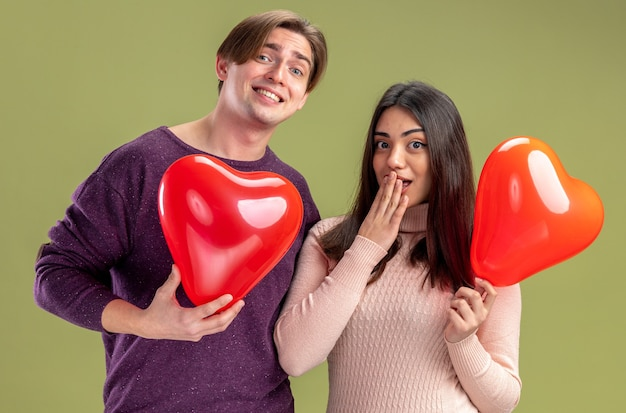 Looking camera young couple on valentines day holding heart balloons isolated on olive green background