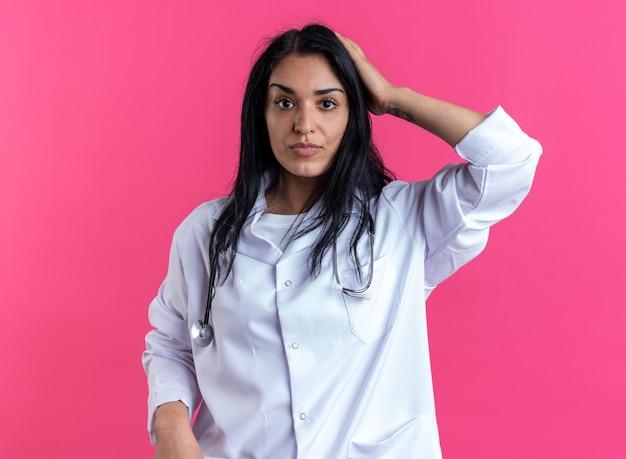 Guardando la telecamera giovane dottoressa che indossa un abito medico con uno stetoscopio che mette la mano sulla testa isolata sulla parete rosa pink