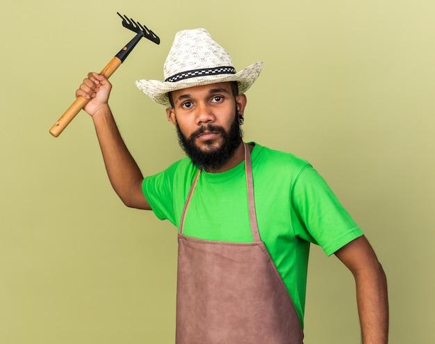 Guardando la telecamera giovane giardiniere afro-americano che indossa un cappello da giardinaggio che tiene rastrello