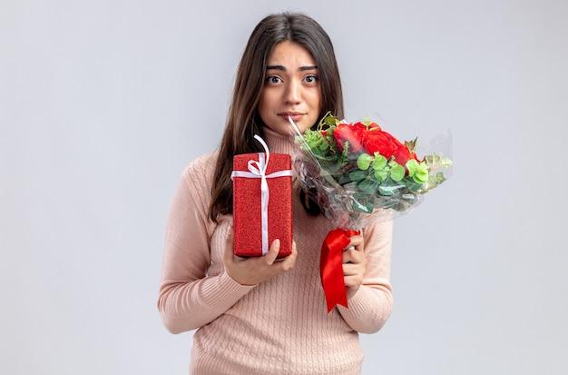 Молодая девушка смотрит в камеру на день святого валентина, держа подарочную коробку с букетом на белом фоне