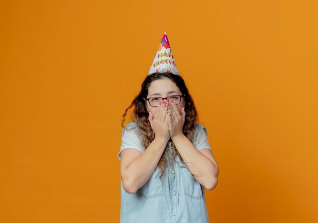 Guardando la fotocamera giovane ragazza con gli occhiali e il cappello di compleanno coperto con le mani bocca isolata su sfondo arancione