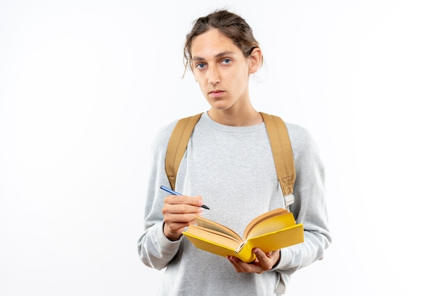 Guardando la fotocamera giovane studente ragazzo che indossa uno zaino che tiene il libro isolato sul muro bianco