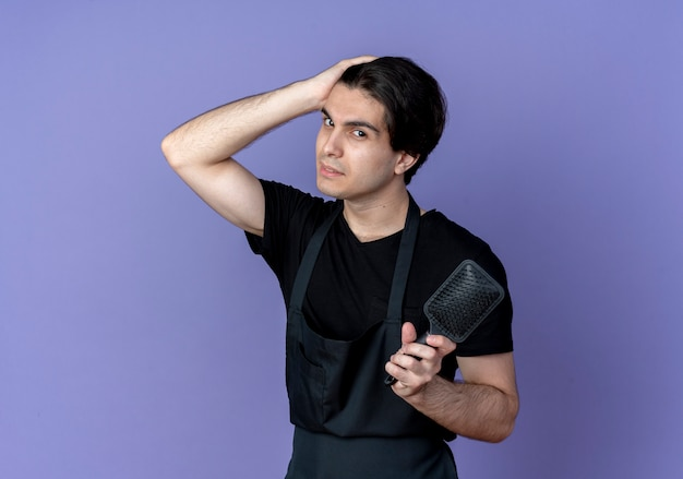 Looking at camera young handsome male barber in uniform holding comb and putting hand on head isolated on blue background