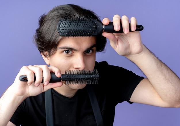 Guardando la fotocamera giovane bel maschio barbiere in uniforme che tiene pettini sulla fronte e sulla bocca isolato su sfondo blu