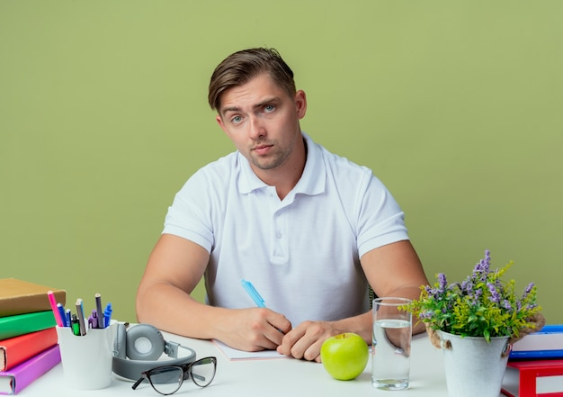 Looking at camera young handsome male student sitting at desk with school tools holding pen isolated on olive green