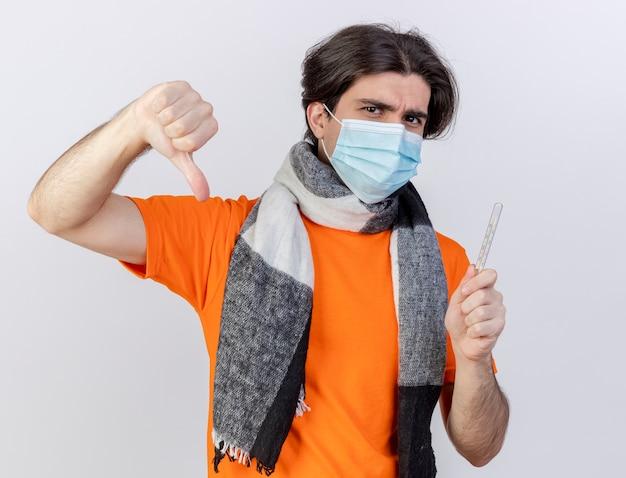 Guardando la fotocamera giovane uomo malato che indossa sciarpa e maschera medica tenendo il termometro che mostra il pollice verso il basso isolato su sfondo bianco