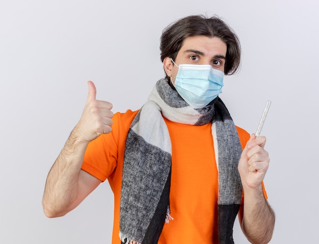 Guardando a porte chiuse giovane uomo malato che indossa sciarpa e mascherina medica tenendo il termometro che mostra il pollice in alto isolato su sfondo bianco