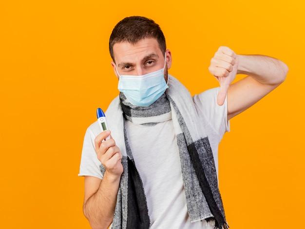 Guardando la fotocamera giovane uomo malato che indossa un cappello invernale e maschera medica tenendo il termometro che mostra il pollice verso il basso isolato su sfondo giallo