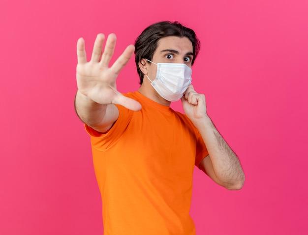 Guardando la fotocamera giovane uomo malato che indossa un cappello invernale con sciarpa e mascherina medica che mostra il gesto di arresto isolato su sfondo rosa