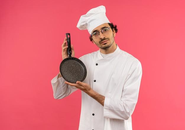 Guardando la fotocamera giovane maschio cuoco indossa divisa da chef e bicchieri tenendo padella