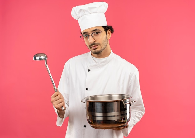 Guardando la fotocamera giovane maschio cuoco che indossa la divisa da chef e bicchieri tenendo pentola e mestolo