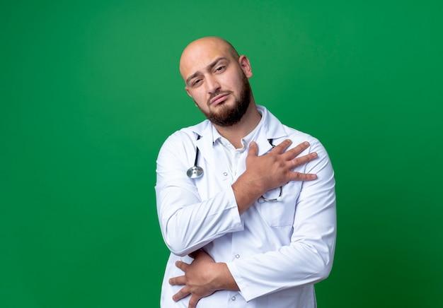 Guardando a porte chiuse giovane medico maschio indossa abito medico e stetoscopio mettendo la mano sulla spalla isolato su sfondo verde