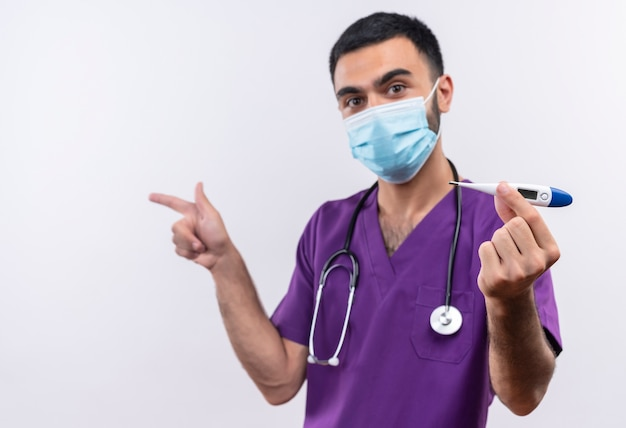 Looking to camera young male doctor wearing purple surgeon clothing and stethoscope medical mask holding thermometer points at side on isolated white background