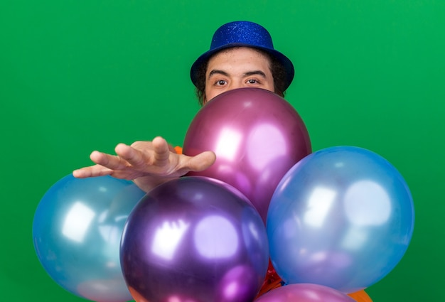 Looking camera young man wearing party hat standing behind balloons holding out hands at camera