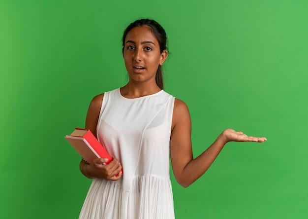 Guardando la fotocamera giovane studentessa tenendo il libro con il taccuino e punti con la mano a lato