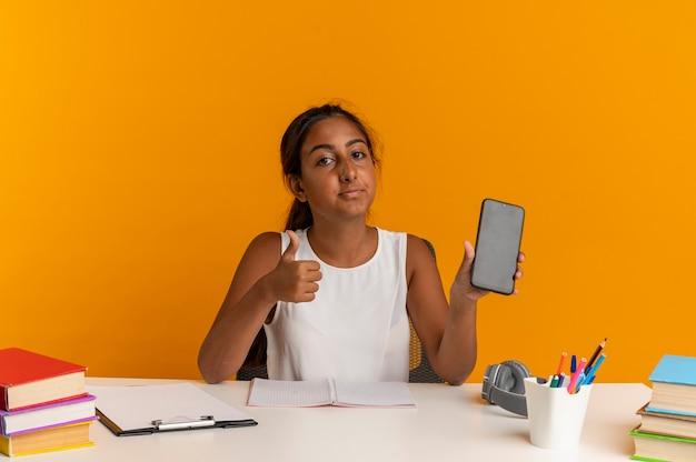 Guardando la fotocamera giovane studentessa seduto alla scrivania con strumenti di scuola tenendo il telefono il pollice in su