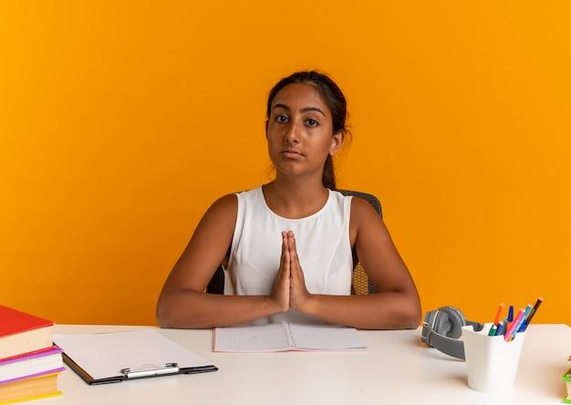 Guardando la fotocamera giovane studentessa seduto alla scrivania con strumenti di scuola che mostra pregare gesto