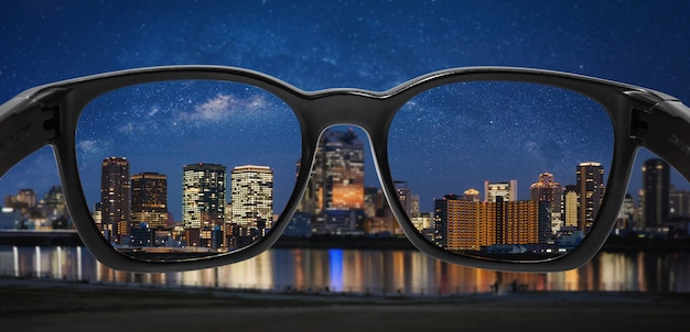 Looking city at night with starry sky through glasses
