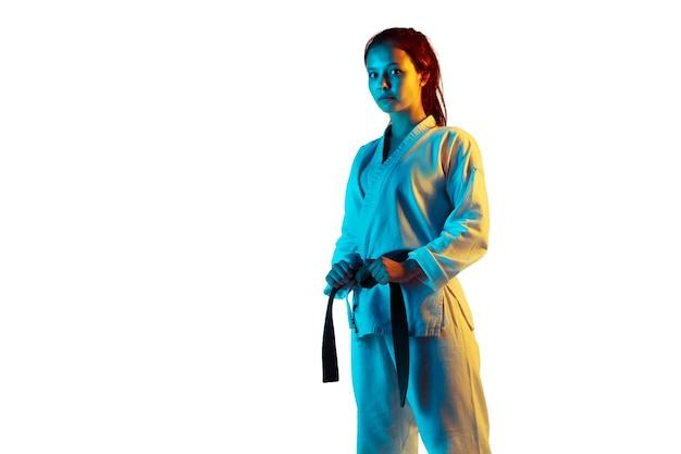 Looking. confident junior in kimono practicing hand-to-hand combat