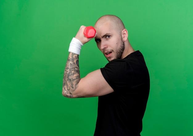 Уверенный в себе молодой спортивный мужчина в браслете, держащий гантели на лбу