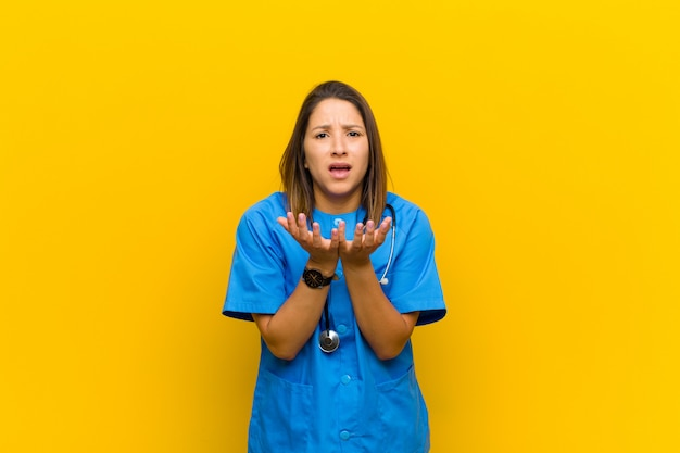 Looking desperate and frustrated, stressed, unhappy and annoyed, shouting and screaming isolated against yellow wall