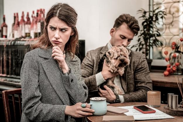 Выглядит разочарованным. женщина выглядит разочарованной, сидя в кафе со своим партнером