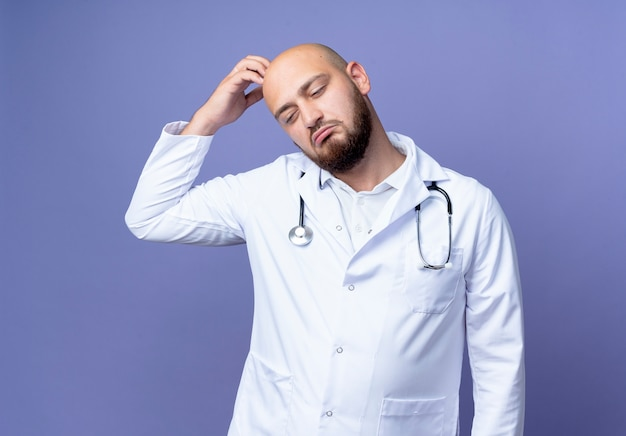 Looking at down confused young bald male doctor wearing medical robe and stethoscope scratching head isolated on blue background