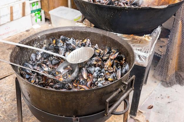 Заглядывать в большую кастрюлю с горячими мидиями на пару с щелевой ложкой готовить на открытом воздухе