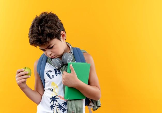 Guardando giù triste ragazzino scolastico indossando la borsa posteriore e le cuffie che tengono mela e libro isolato su sfondo giallo con spazio di copia